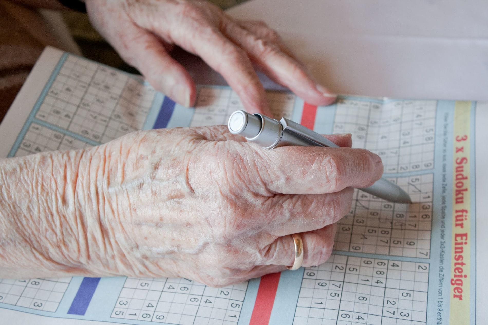 Foto der Hände einer älteren Frau beim Lösen eines Sudoku-Rätsels