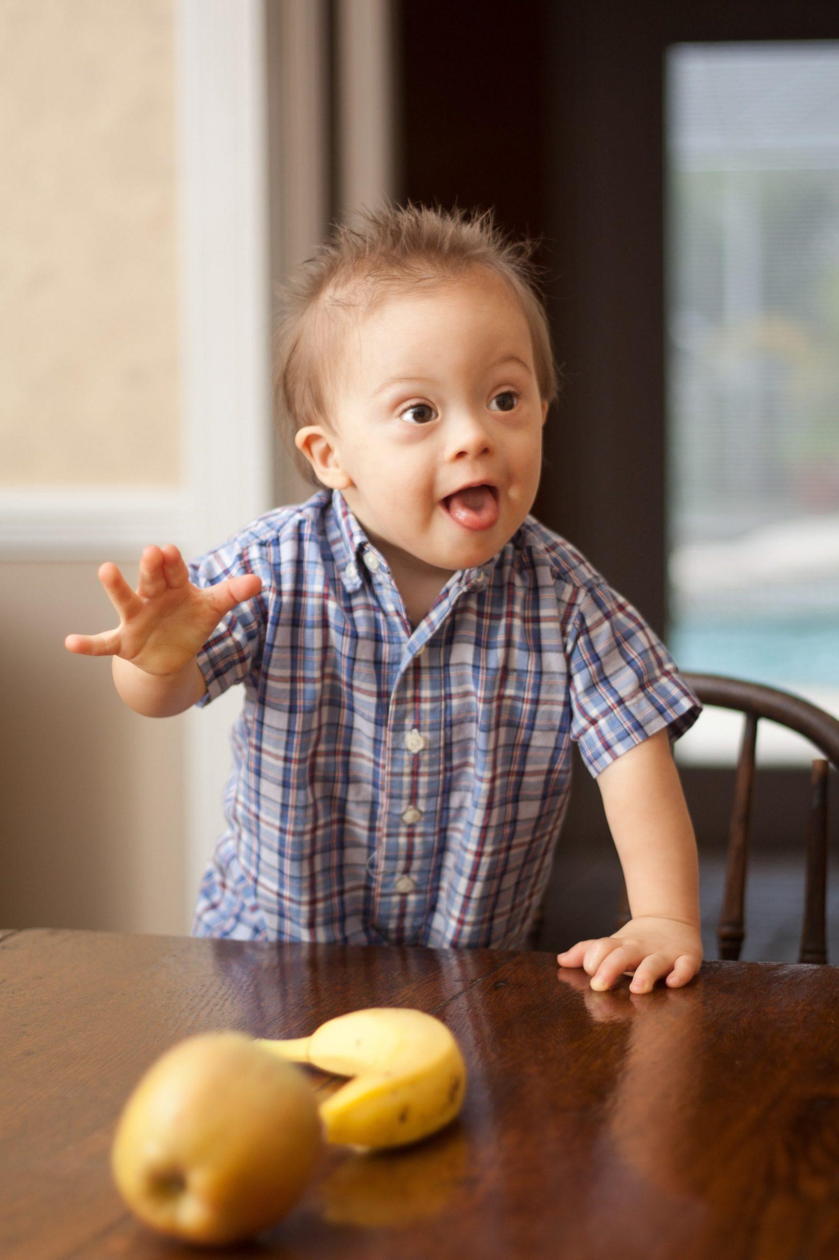 Foto eines kleinen Jungen, der nach Obst greift